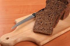 El baguette francés cortó en el tablero de pan de madera con el cuchillo Fotos de archivo
