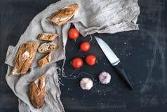 El baguette francés cortó en pedazos, los cereza-tomates, el ajo y el cuchillo de cocina sobre fondo oscuro del grunge Fotografía de archivo libre de regalías