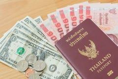 El baht del dólar carga en cuenta el pasaporte tailandés de las monedas Imagen de archivo libre de regalías