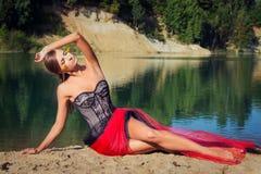 El bailarín atractivo hermoso de la muchacha se sienta en las orillas del día de verano brillante del lago Fotos de archivo libres de regalías