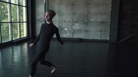 El bailarín de ballet hace un salto de altura y una pirueta baile del hombre joven contra un fondo oscuro en el estudio Cámara le almacen de metraje de vídeo