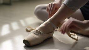 El bailarín de ballet implica sus pointes Bailarín de ballet que ata los zapatos de ballet antes de entrenar almacen de video