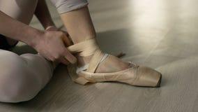 El bailarín de ballet implica sus pointes Bailarín de ballet que ata los zapatos de ballet antes de entrenar imagenes de archivo