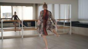 El bailar?n de la mujer en trenes del vestido baila delante del espejo en el sal?n de baile almacen de video