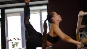 El bailar?n de la mujer joven con la cola de caballo larga en medias muestra la flexibilidad del cuerpo que sostiene la barandill almacen de metraje de vídeo