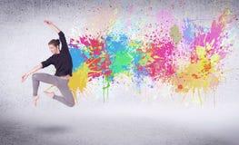 El bailarín moderno de la calle que salta con la pintura colorida salpica Imagen de archivo libre de regalías
