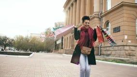El baile atractivo de la muchacha de la raza mixta y se divierte mientras que camina abajo de la calle con los bolsos Mujer joven foto de archivo libre de regalías