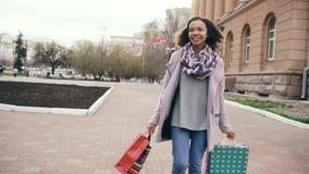 El baile atractivo de la muchacha de la raza mixta y se divierte mientras que camina abajo de la calle con los bolsos Mujer joven Imagen de archivo