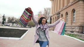 El baile atractivo de la muchacha de la raza mixta y se divierte mientras que camina abajo de la calle con los bolsos Mujer joven Fotografía de archivo libre de regalías
