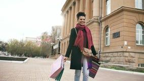 El baile atractivo de la muchacha de la raza mixta y se divierte mientras que camina abajo de la calle con los bolsos Mujer joven Fotos de archivo libres de regalías