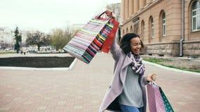 El baile atractivo de la muchacha de la raza mixta y se divierte mientras que camina abajo de la calle con los bolsos Mujer joven Imágenes de archivo libres de regalías