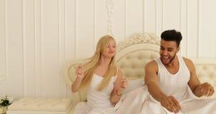 El baile de la cama de los pares que se sienta mezcla a la mujer del hombre de la raza que juega teniendo dormitorio de la divers almacen de metraje de vídeo