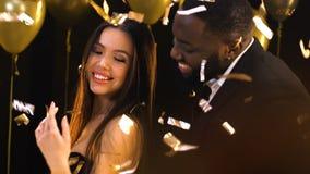 El baile del hombre negro con la mujer asiática en el club nocturno debajo del confeti que cae, se relaja almacen de video