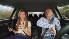 El baile divertido del muchacho en el coche y la muchacha que usa la tableta 4K almacen de metraje de vídeo