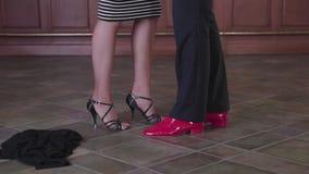 El baile, el hombre y la mujer de los pares sacan su ropa, después beso, piernas metrajes