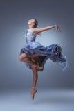 El baile hermoso de la bailarina en vestido largo azul Imágenes de archivo libres de regalías