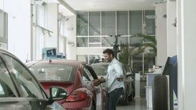 El baile moreno feliz del individuo cerca del coche y muestra un pulgar para arriba en concesión de coche almacen de metraje de vídeo