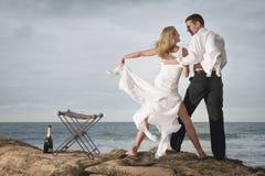 El baile romántico joven de los pares en la playa oscila con champán fotografía de archivo libre de regalías