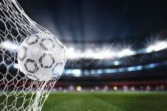 El balón de fútbol anota una meta en la red representación 3d foto de archivo libre de regalías