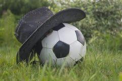 El balón de fútbol cubierto con un sombrero Fotos de archivo