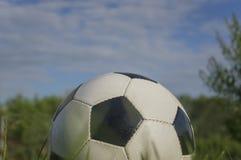 El balón de fútbol en el fondo del cielo Foto de archivo libre de regalías