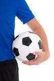 El balón de fútbol en el jugador entrega blanco Fotos de archivo