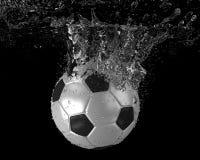 El balón de fútbol se zambulle en el agua Foto de archivo