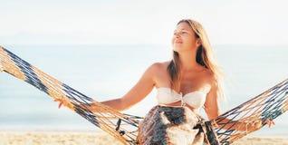 El balanceo femenino sonriente feliz en hamaca se articuló entre las palmeras en el lado de mar imagen de archivo