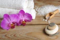 El balneario fijó con la sal blanca para el baño, las flores de la orquídea y las toallas en un fondo de madera Imágenes de archivo libres de regalías