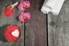 El balneario fijó con la sal de baño, las flores de la orquídea y las toallas en un fondo de madera Foto de archivo
