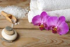 El balneario fijó con las toallas blancas, la sal del mar y las flores brillantes de la orquídea Fotos de archivo