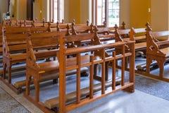 El banco de madera de la iglesia católica, gente puede rogar para dios Jesús Imágenes de archivo libres de regalías