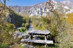 El banco de madera pasa por alto la montaña de Rodopite y el río del iskur Imágenes de archivo libres de regalías