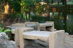 El banco o las sillas de piedra vacío en piscina echa a un lado en parque fotografía de archivo