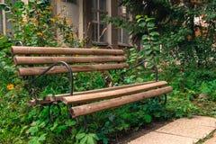 El banco vacío de madera en alto gren la hierba al aire libre en el parque abandonado Imagen de archivo