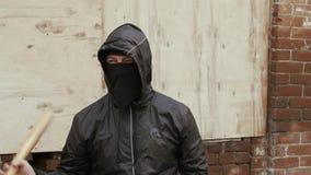 El bandido de la calle en máscara y capilla negras sostiene el bate de béisbol en distrito criminal almacen de video