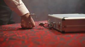 El bandido pone la caja del aluminio de la tabla Límite del caso a las esposas de la mano almacen de metraje de vídeo