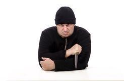 El bandido se sienta con el cuchillo grande Foto de archivo libre de regalías