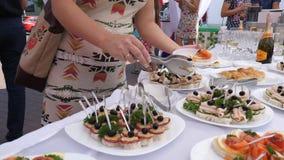El banquete, gente toma la porción de comida en placa de la tabla