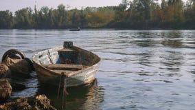 El barco amarrado viejo en un río, más nuevo va rio abajo metrajes
