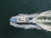 El barco azul y blanco ara la superficie del mar azul, saliendo de un rastro de la espuma La visi?n desde la tapa fotografía de archivo
