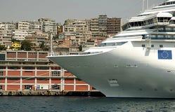 El barco de cruceros atracó en la terminal con la parte posterior de la ciudad encendido Fotografía de archivo