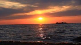 El barco de cruceros de lujo del mar en la puesta del sol y salpica metrajes