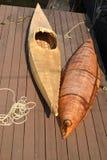 El barco de la corteza de abedul y un kajak mienten en un andamio del tablero Fotografía de archivo