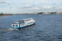 El barco de la excursión con los turistas flota en el río de Neva en St Petersburg, Rusia Foto de archivo