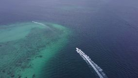 El barco de la visión aérea en el medio del mar azul sale de la isla de Manukan metrajes