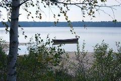 El barco de madera hermoso amarró cerca de la orilla del lago Foto de archivo