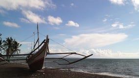 El barco de pesca atracó en la orilla de mar arenosa blanca en el cielo azul claro Lapso de tiempo almacen de video