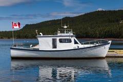 El barco de pesca blanco y azul atracó imagenes de archivo