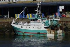El barco de pesca del blanco y de la turquesa atracó junto al embarcadero con el fondo del almacén Fotografía de archivo